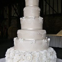 latte and cream wedding cake with floral detail at top and base