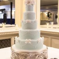 blue and white wedding cake with bow and floral detailing