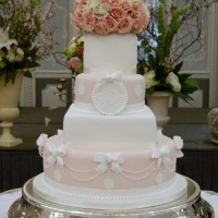 peach and white four tier wedding cake with floral top