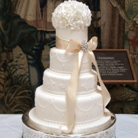 four tier wedding cake, all white with peach ribbon and brooch detail