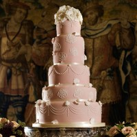 5 tier pink and white detailed cake with floral top